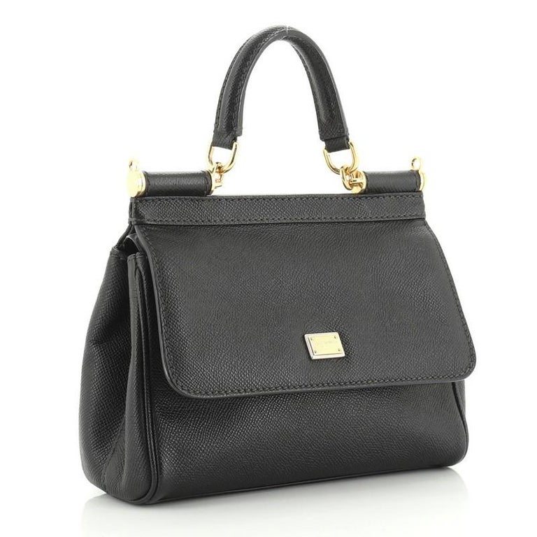 This Dolce & Gabbana Miss Sicily Bag Leather Small, crafted in black leather, features a leather top handle, protective base studs, and gold-tone hardware. Its framed top flap with magnetic snap closure opens to a brown fabric interior with zip and