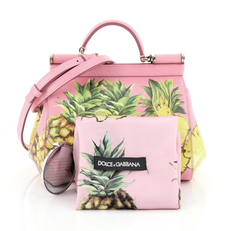 This Dolce & Gabbana Miss Sicily Bag Printed Leather Mini, crafted in pink printed leather, features a single looped leather handle, frontal flap, protective base studs and gold-tone hardware. Its hidden magnetic snap closure opens to a pink leather