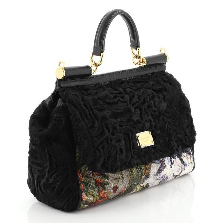 This Dolce & Gabbana Miss Sicily Bag Velvet and Crochet Medium, crafted in black printed velvet and crochet, features a flat top handle and gold-tone hardware. Its framed top flap with magnetic snap closure opens to a brown printed fabric interior