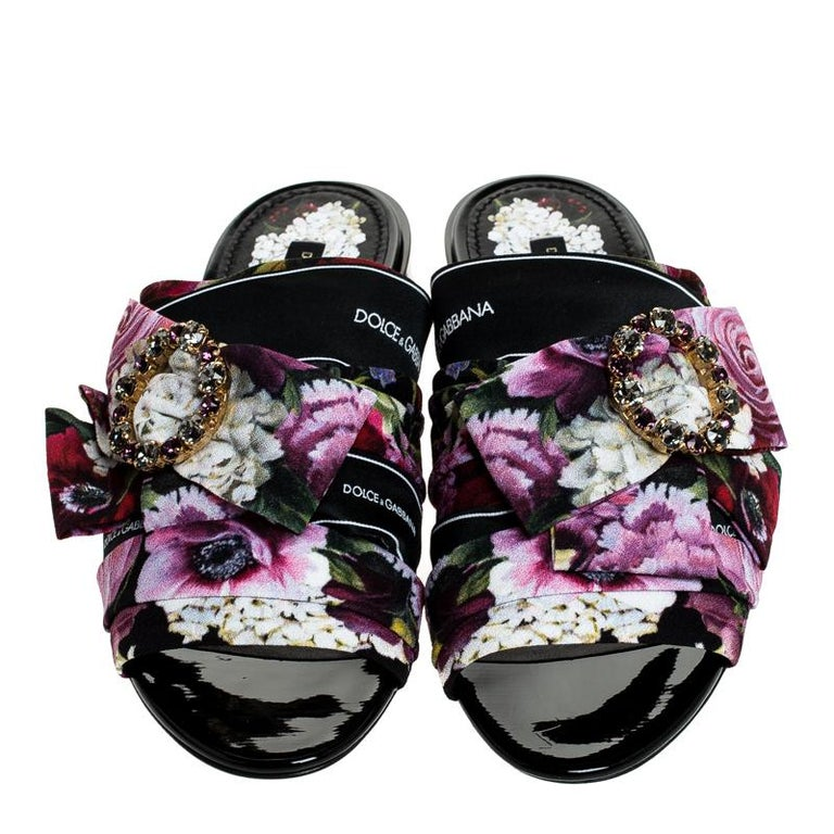 Elegant with a lush floral-printed fabric exterior, these easy slip-on mules from Dolce & Gabbana are pretty and feminine. They are designed with open toes, embellished buckles with bows and short heels carrying the brand name.  Includes: Original