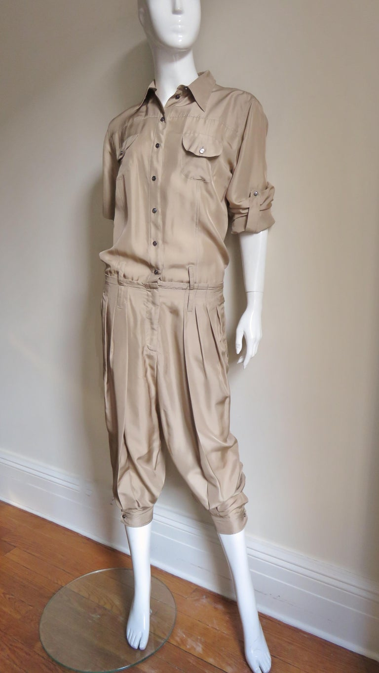 A fabulous khaki silk jumpsuit by Dolce & Gabbana.  It has a shirt collar, 2 breast button flap pockets and a drop waistline.  The long sleeves have a 1 button cuff and the ability to be pulled or folded up above the elbow and held in place with a