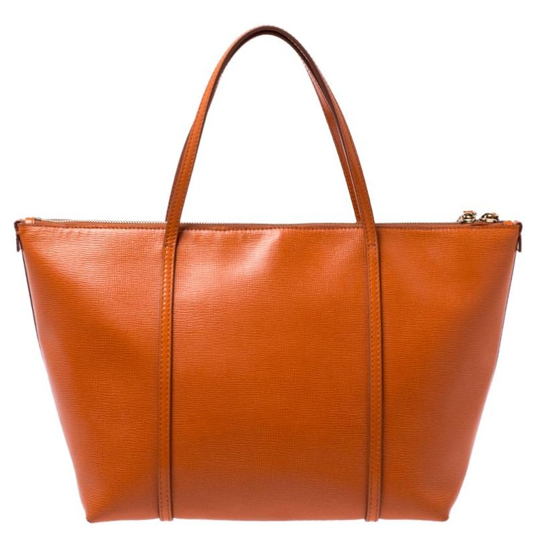 This stunning Escape shopper tote is from the house of Dolce & Gabbana. Crafted from leather, and lined with suede on the insides, the bag features a bright orange exterior with dual top handles and a gold-tone padlock flaunted on the front. Swing