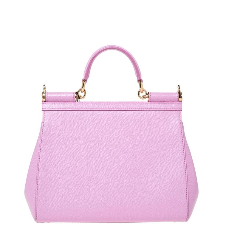 This gorgeous pink Miss Sicily bag from Dolce & Gabbana is a handbag coveted by women around the world. It has a well-structured leather exterior and flap that opens to a compartment with enough space to fit your essentials. The bag comes with