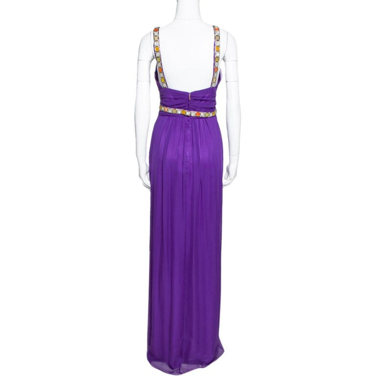Designed in a flattering silhouette, this silk chiffon maxi number from Dolce & Gabbana is a head-turner! It looks lovely in a purple shade and features ruched details throughout. It flaunts beads and crystals embellished on the waist and the
