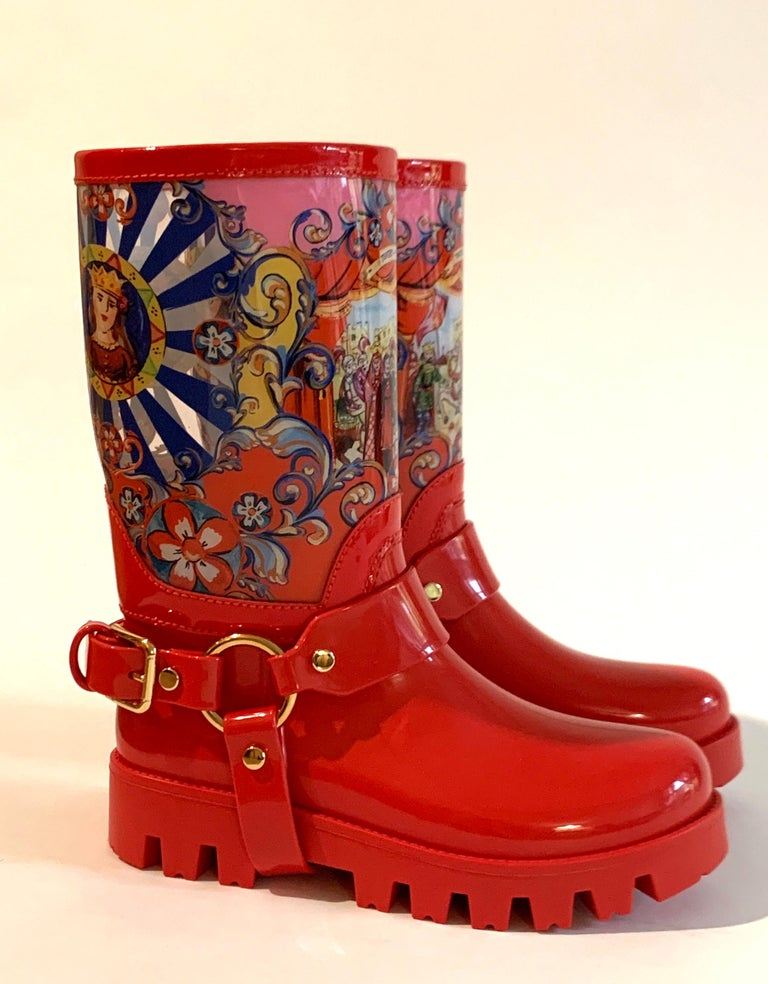 Dolce & Gabbana red PVC printed rain boots. Clear uppers feature a female portrait, Teatro di Pupi scene, and flowers. buckle detailing at ankles. Pull on.   Made in Italy.  Size IT 36, approximate US 6.  Excellent, unworn condition. Box included,