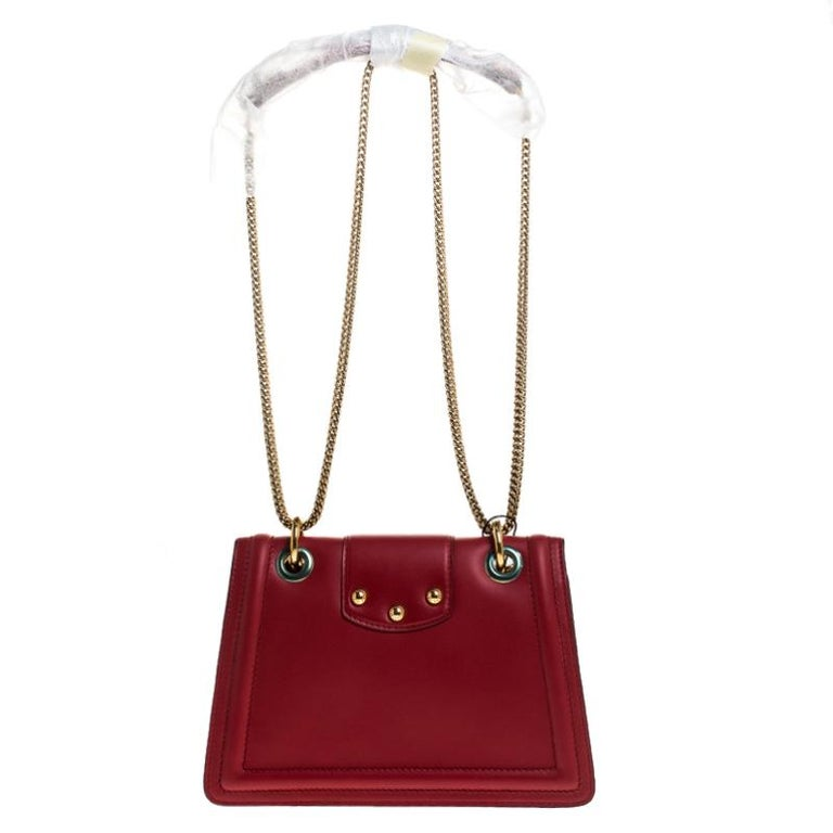 Well-structured and high on style, this DG Amore bag from Dolce & Gabbana deserves to be yours! It has been crafted from red leather and styled with chain-link shoulder straps. It also comes with gold-tone embellished logo detail on the flap that