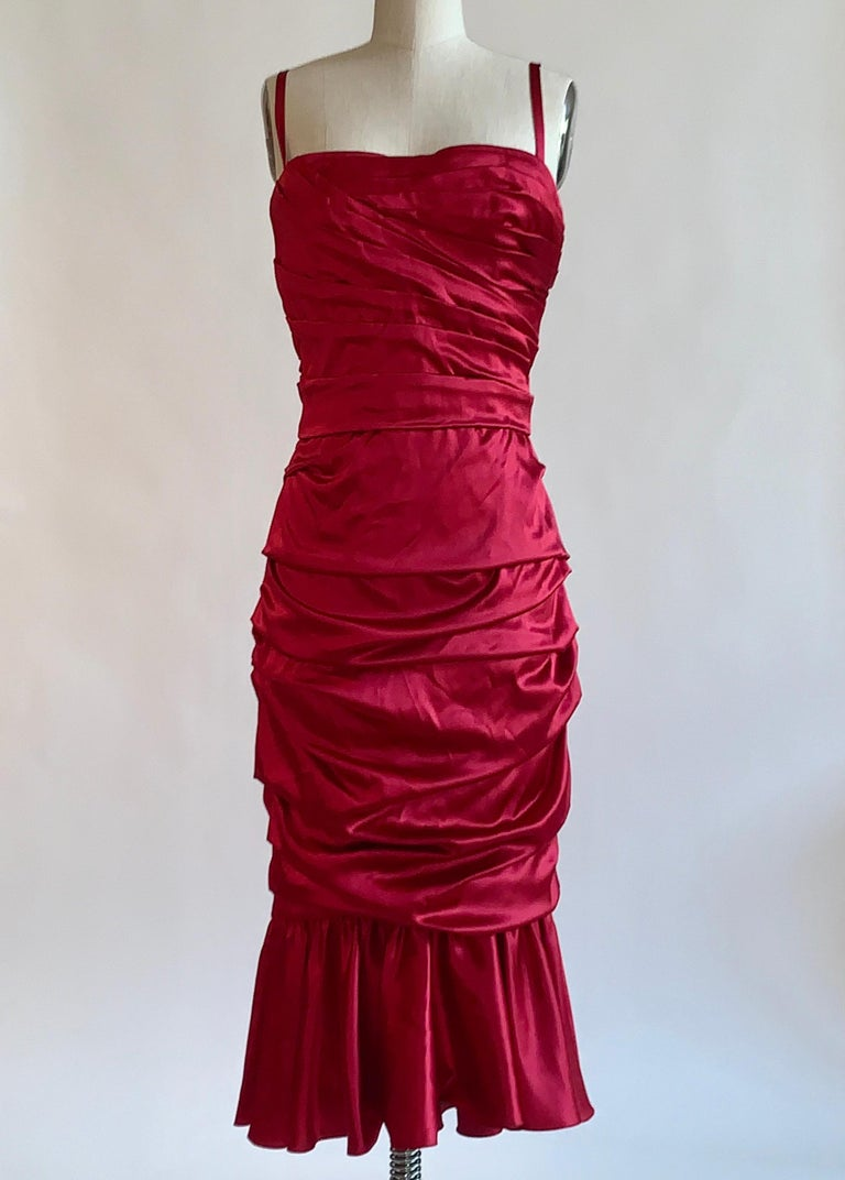 Dolce & Gabbana red ruched silk satin cocktail dress with thin straps and ruffled flounce hem. Built in corset at top. Back zip.   96% silk, 4% spandex. Fully lined in 66% silk, 15% cotton, 11% spandex, 8% polyamide.  Made in Italy.  Labelled size