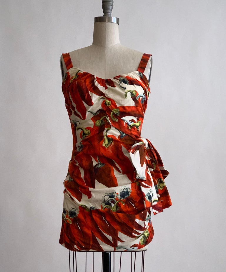 Dolce and Gabbana red and white pepper print mini dress. Ruched bodice, bow detail at side. Built in corset detailing at interior. Back zip and hook and eye. Spring 2012 Runway Look 5.  100% cotton. Fully lined in 96% silk, 4% elastane.  Made in