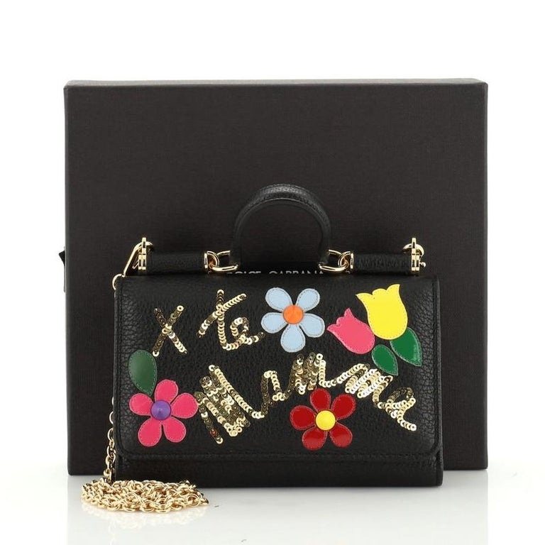 This Dolce & Gabbana Sicily Wallet on Chain Embellished Leather Mini, crafted from black and multicolor embellished leather, features a short top handle, designer plaque, framed top, and gold-tone hardware. Its snap closure opens to a black leather
