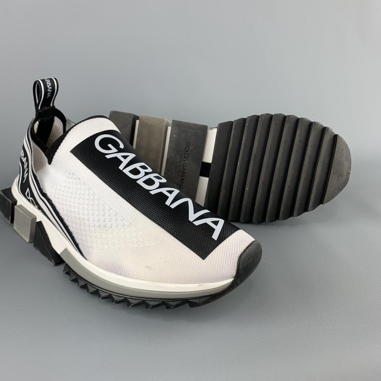DOLCE & GABBANA Sorrento sneakers come in white knit with logo tape effect motif, printed elastic bands, and grey color block rubber sole. Made in Italy.  Very Good Pre-Owned Condition. Marked: (no size)  Outsole: 12 x 4.5 in.