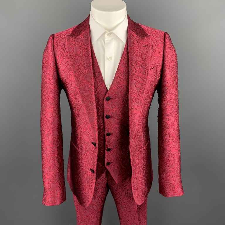 DOLCE & GABBANA suit comes in a vibrant raspberry fuchsia pink brocade and includes a single breasted, two button, peak lapel sport coat, matching V neck vest, and tailored dress pants. Made in Italy.  New with Tags. Marked: IT