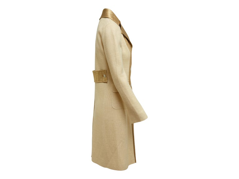 Product details: Tan and gold long coat by Dolce & Gabbana. Notch collar. Dual flap pockets at hips. Button closures at center front. Designer size 40. 35