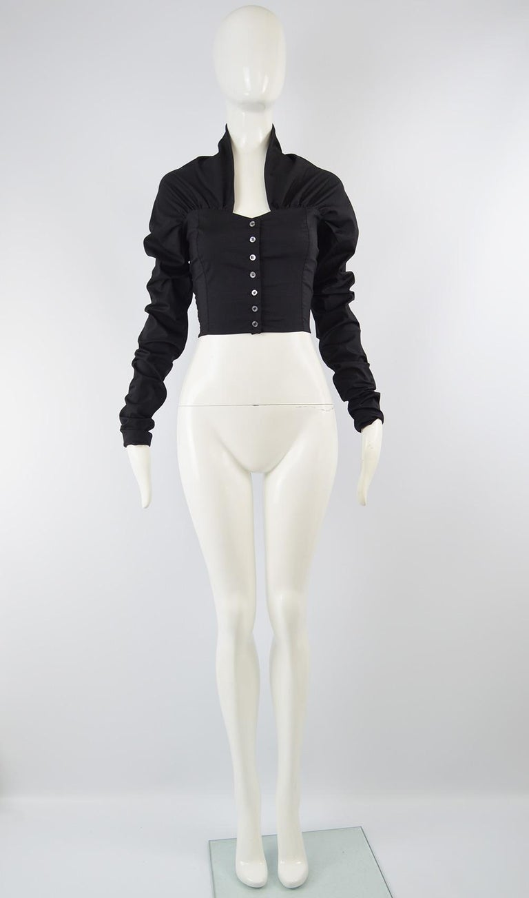 An incredible avant garde women's blouse from the 90s by Dolce & Gabbana. In a black stretch silk and lycra blend, the sleeves are extra long and bunch up to create a ruched effect. The back has a stand up collar almost like a half shawl collar,