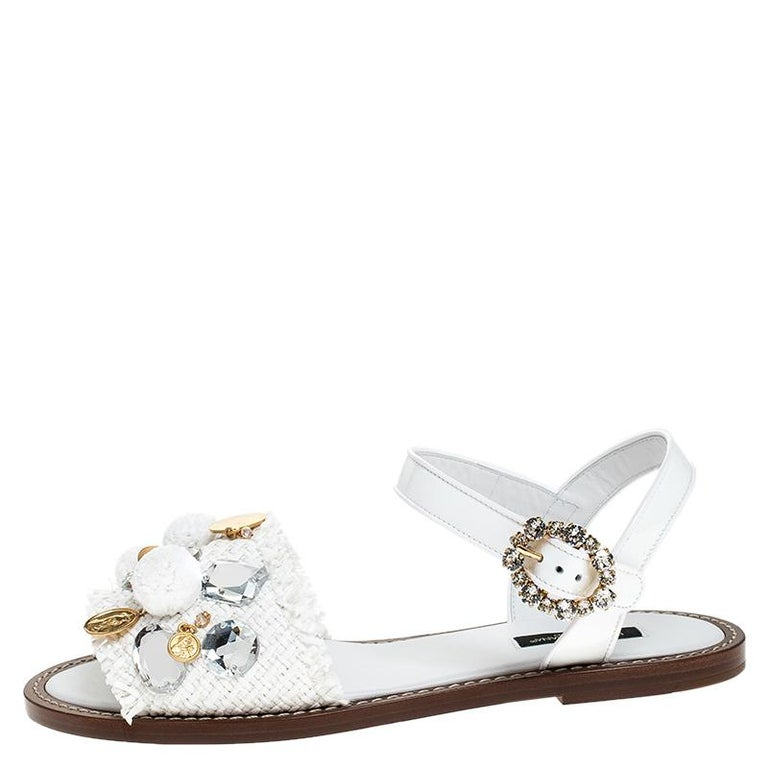 Dolce & Gabbana never fails to impress and manages to win our hearts every time! These white sandals are crafted from patent leather and feature an open toe silhouette. They flaunt the raffia straps on the toes accented with pom-poms and coin