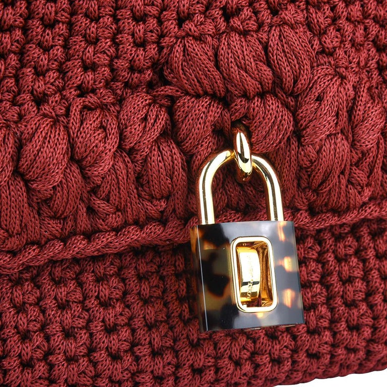 Guaranteed authentic Dolce&Gabbana Crochet hand / shoulder bag. Jewel toned Burgundy crochet bag with rich texture.  Handle is gold chain and red snakeskin. Front closure is a faux tortoise lock with logo embossed turnkey. Bag has 1 interior zip