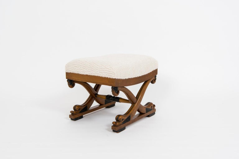 A 20th century maple stained giltwood Curule bench newly upholstered in a soft nubby bouclé wool.