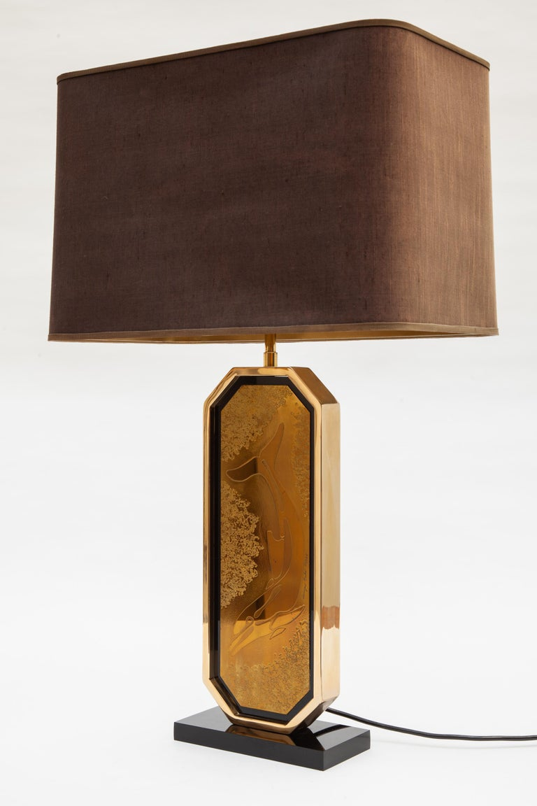 Vintage table lamp by Designo Mahó, Belgium. Gold base with black Lucite accents. Features a dolphin etching by artist Georges Mathias, signed and numbered 50/125. Raw silk shade with adjustable height. Holds two bulbs.  Measures: 20 W x 9 D x 75