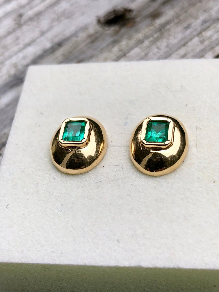 The emerald are bezel set in these classic style button earrings. The 18k yellow gold, high profile domes are a rich high polished finish stylish dome earrings Colombian emerald. Primary Stone: Natural Colombian Emerald Shape or Cut: Emerald Cut