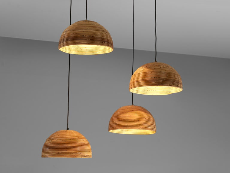 Dome pendants, bamboo bentwood, brass, Europe, 1960s  These pendants are made out of bentwood bamboo which is layered horizontally and forms a dome shape light. The warm color of the natural material presents a soft lighting indoors as well as in