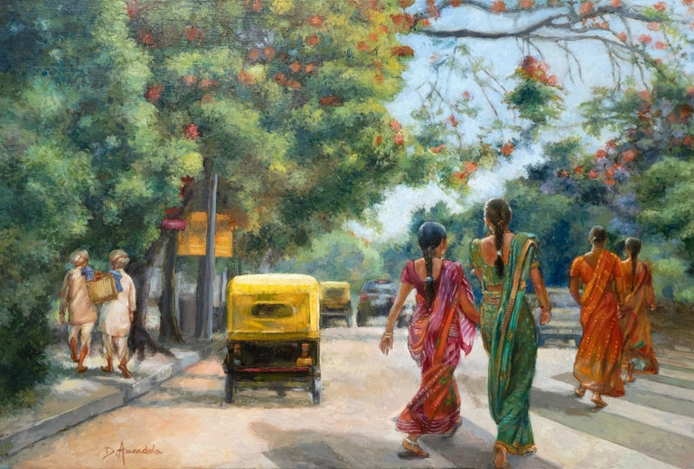 Ladies in colorful saris are crossing the street in Bangalore, South India. The trees are full of reddish flowers and extend across the street. Some typical yellow rickshaw is visible on the left. Some traditionally dressed old Indian gentlemen are