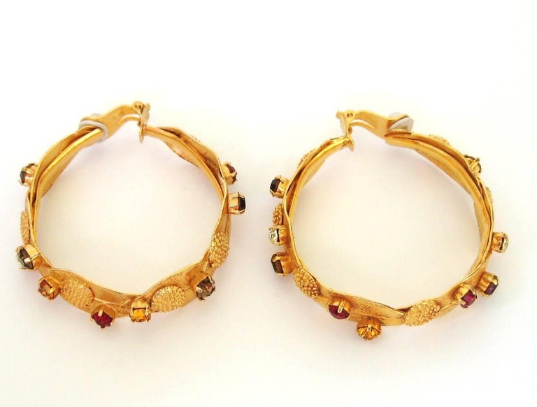 These are Fabulous Hoop earrings, from a collection of Dominique Aurientis. Oversized gilt metal hoops with prong set colored crystals set all around the entire hoop. Clip On style earrings. 2.19 inches. We have many more pieces on our storefront.