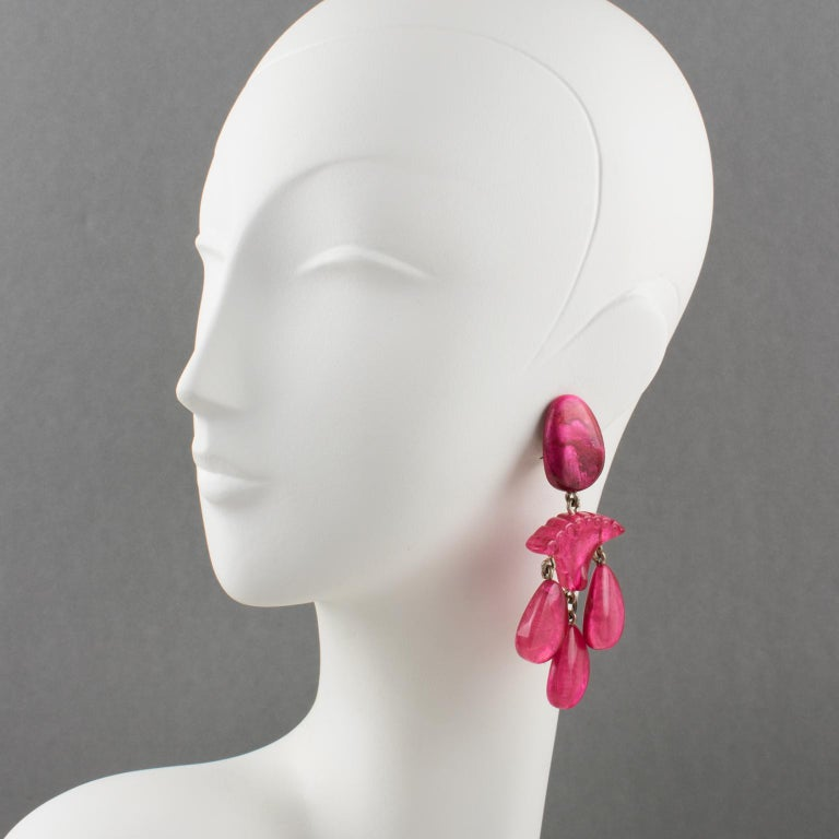 Stunning oversized clip-on earrings by Dominique Denaive Paris. Sculptural chandelier dangling shape, with carved resin, and drop charms in unusual moonglow hot pink color. Signed at the back of one earring with metal tag