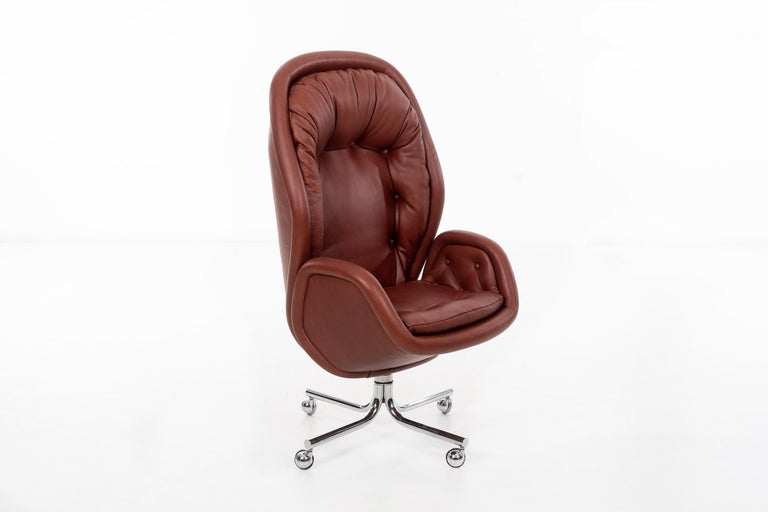 Sculptural executive desk chair. Newly upholstered with foam in Spinneybeck leather, on chrome-plated base. Chair features adjustable height, swivels, and reclines.