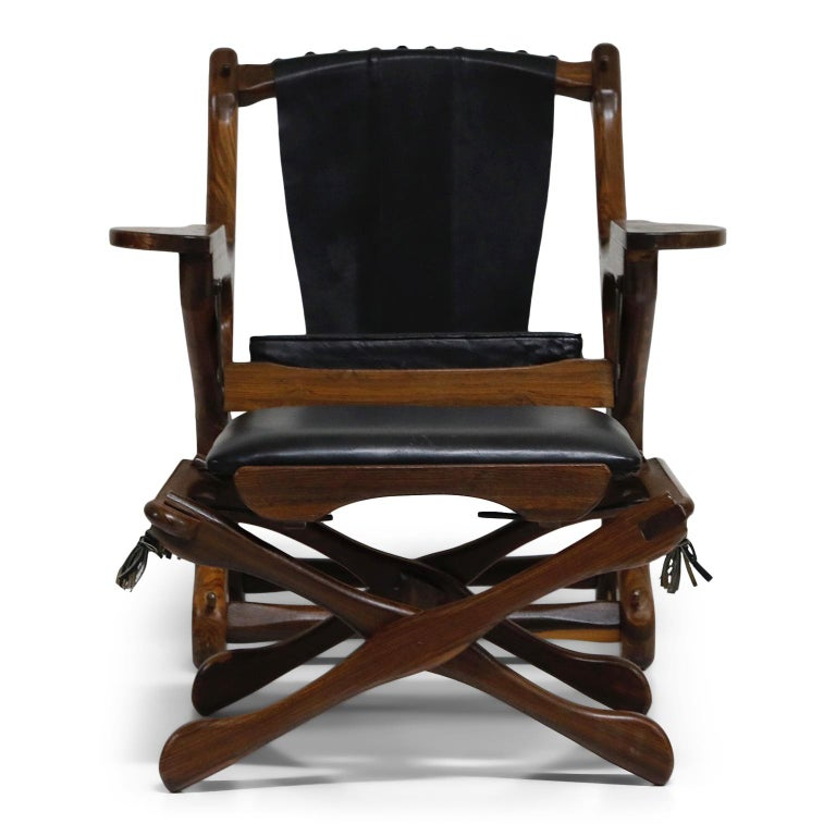 Named the 'Swinger Chair' for its pivoting mechanism that allows you to swing in your seat, this incredible Cocobolo Rosewood and black leather 'Swinger' chair with matching ottoman by leading 1960s modernist designer Don Shoemaker for Senal S.A.