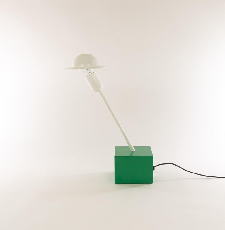 Don table lamp designed in 1977 by Ettore Sottsass and manufactured by Stilnovo.  The lamp consists of a relative heavy emeraldgreen cubic base, a white slanted rod and a striking adjustable white shade. This shadeis connected to the light bulb