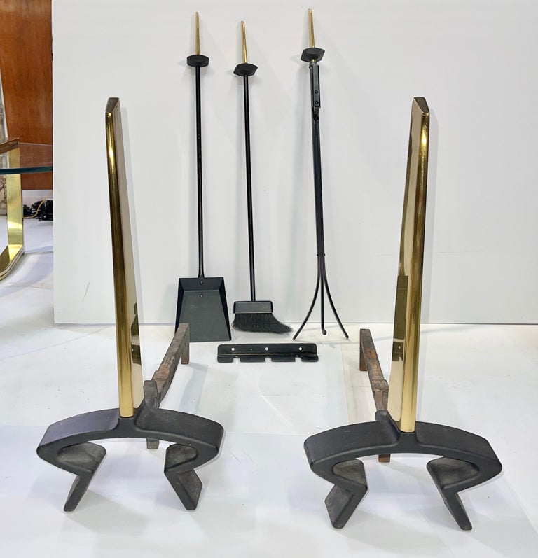 An original five piece set of modernist Art Deco andirons and matching fireside tools designed by Donald Deskey and produced by Bennett-Ireland Company of Norwich, NY. Sculptural hefty brass handles on the broom, shovel and claw poker. The three