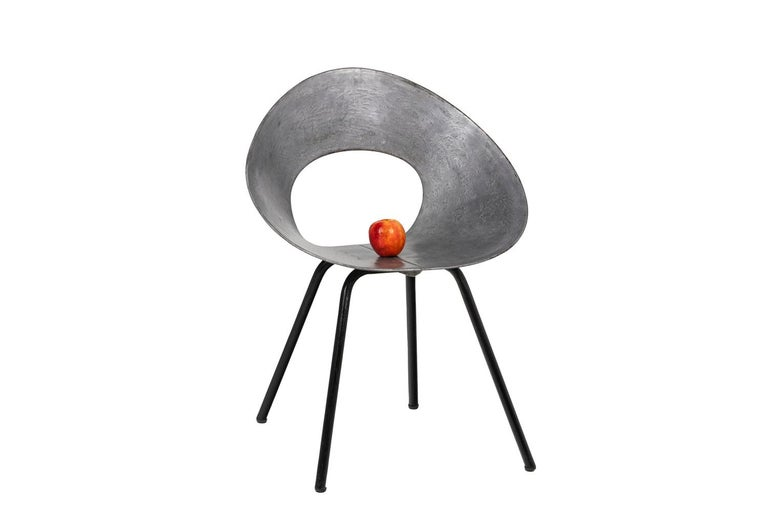 Donald Knorr for Knoll, signed.  132U chair whose seat and back are made of a metal curved and galvanized ribbon in steel and forming an cone drilled in its center and maintened in shape by bolting on a tubular base with four legs in painted