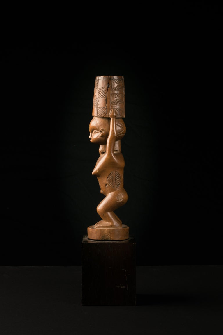 Flywhisk handle sculptured in the form of a woman with slightly bended Knees and Scarification's on different parts of her body. She is holding a vessel that kept a ponytail. This Flywhisk was part of a Chief's Regalia. Provenance: ancient