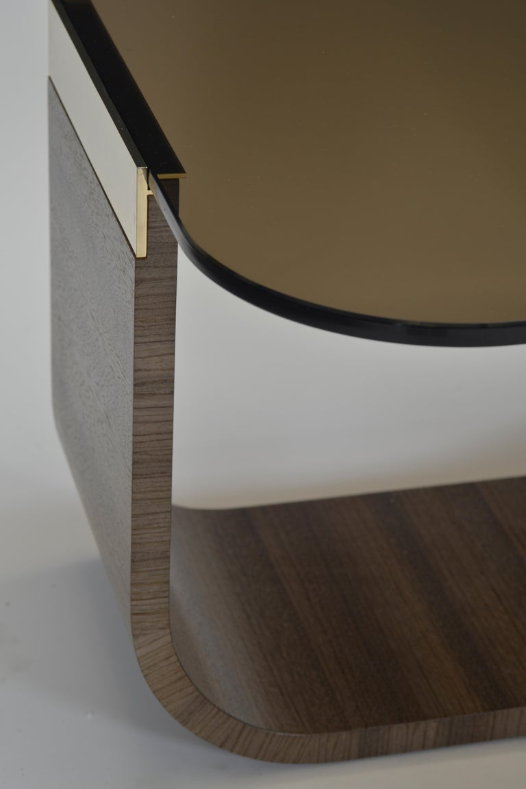Cocktail table with gold-plated accents in choice of grigio leather or gray Zebrano veneer. The leather base comes standard with stitching accenting the perimeter. Options for the top include bronze glass or white limestone. Overall dimensions of