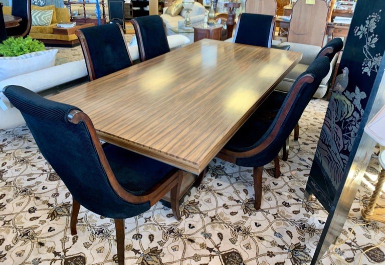 A rare and coveted Donghia London Laurent eight foot dining table which features two pedestals bases, each consisting of four posts on a flared square base. Each post tapers and curves narrow towards the top, presenting the Lauren tabletop as a