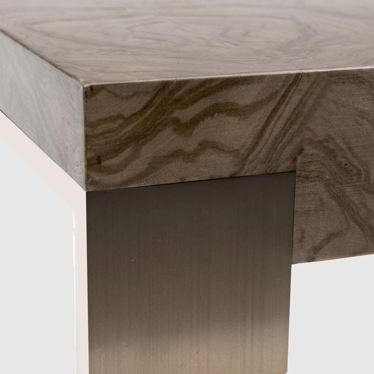 End table with top veneered in olive ash burl with a warm gray stain supported by a stainless steel base in an antique satin finish with polished edges. Carton packaging included.