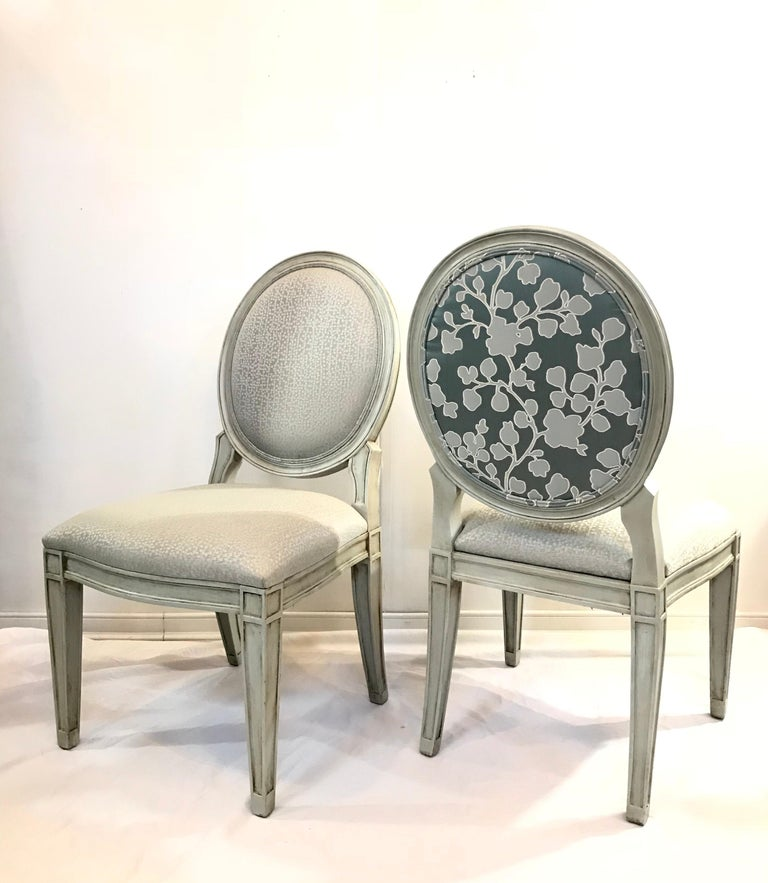 A striking set of vintage Donghia style dining chairs dressed up in a sleek custom greige finish. The Rounded tops are dramatized further by the use of a brilliant silk blended floral scene fabric on the back of each chair. Well proportioned for