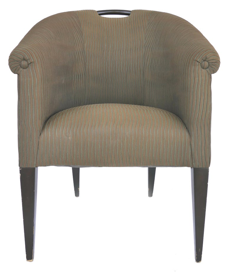 Donghia upholstered club chairs with wood handles  Offered for sale is a pair of upholstered club chairs by Donghia with a wooden handle at the top and sides that slant down to the arms. The chairs are supported by slender tapered legs. The chairs