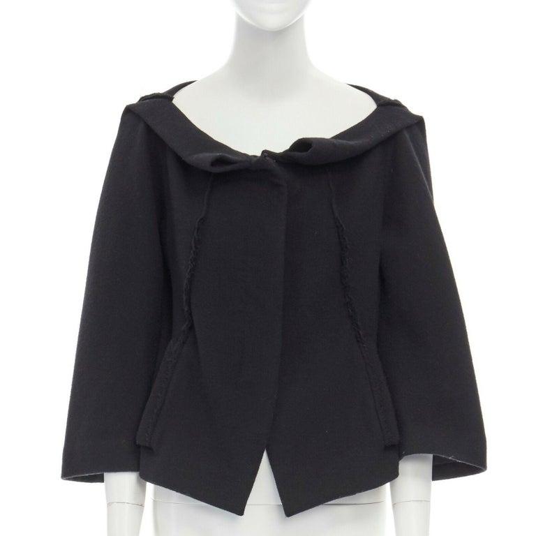 DONNA KARAN black wool blend frayed seam concealed button wide neckline jacket S  DONNA KARAN Wool, polyamide, spandex. Black. Wide collar. Folded collar. Frayed seams at front and along shoulder seam. Concealed button front closure. Dual front