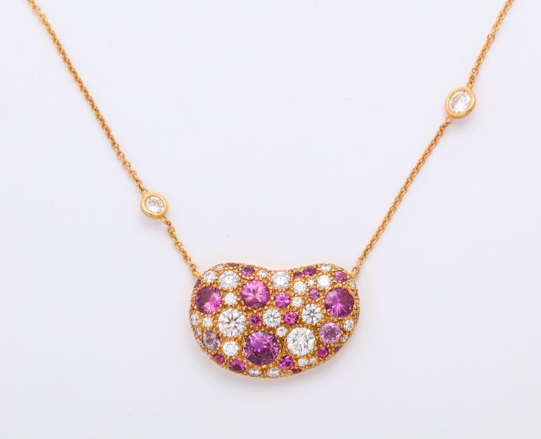 A lively precious stones pendant necklace inspired by the artist's palette used while rendering her jewelry collection, is created in 18 karat pink gold and set with 29 round hot pink sapphires totaling 2.41 carats and 41 round brilliant white