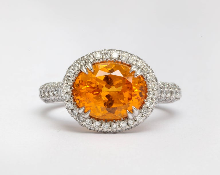 A vivid orange, crystal clean garnet gem. Skillfully crafted platinum ring featuring an oval brilliant cut 3.99 carat mandarin garnet.  Also known as Spessartite, with micro pavé-set diamonds for a rolled affect setting. Total weight of diamonds is
