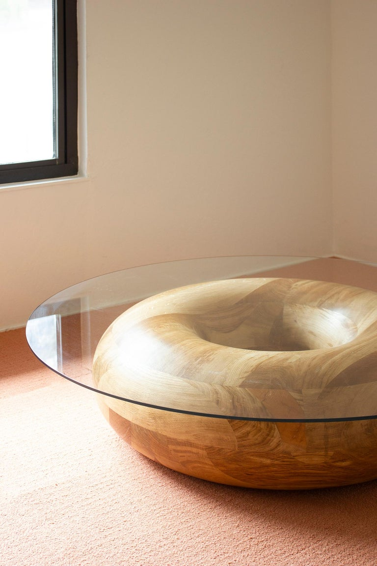 True to its name, the doughnut coffee table is a dense swirl of solid oak, rich with varying grain and gradient in a clear caramel finish. Topped with a round glass top, the doughnut functions as an ideal coffee, cocktail or conversation table.