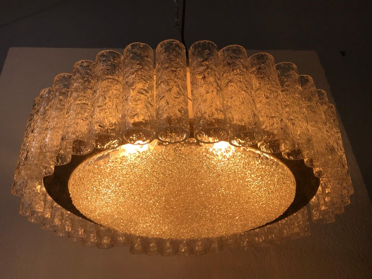 A Doria ice glass chandelier made in Germany in the 1960s. It is fascinating with its many ice tubes. The 40 frosted glass tubes are surrounded by a brass disc with patina. The light has a metal frame at the body.  Measurements:  Height 57
