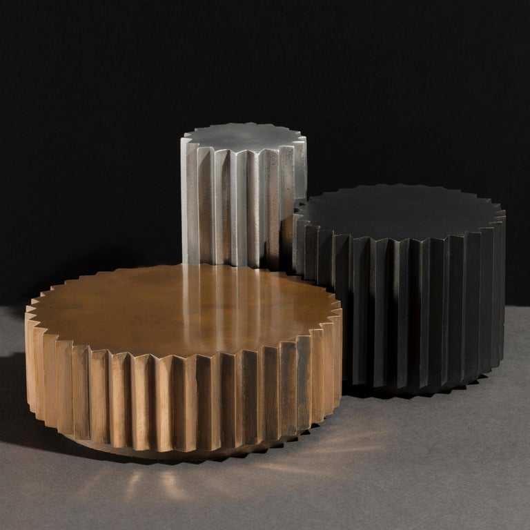 Side tables in cast bronze, blackened bronze or aluminum of different diameters and heights that can be combined to create a coffee table. Inspired by Doric columns in archaic architecture, the extruded multi-point stars have a different finish on