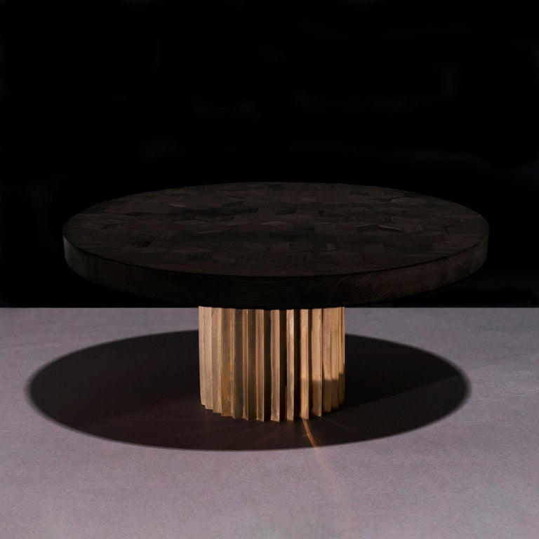 Dining or entrance table with marquetry top in ebonized Oak and multifaceted pedestal in cast bronze.   The marquetry tabletop in reclaimed Oak contains 222 rhombi cut from old Italian wine barrels. Inspired by Doric columns in archaic architecture,