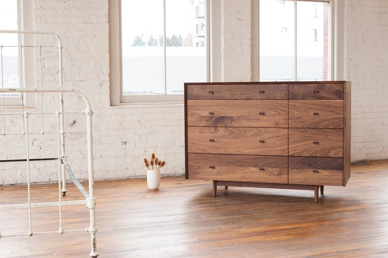 Phloem Studio Dorothy Bureau solid walnut wood chest of drawers. The hardwood case has a grain matched waterfall miter from side to top to side. The drawer fronts are grain matched. 8 solid maple wood drawers slide easily with self closing slides.