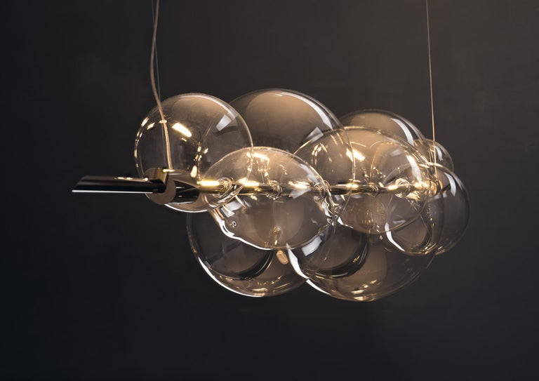An exquisite exercise in balance, this chandelier exudes a Minimalist flair marked by clean and essential lines. Its dimmable structure features two brass bars hanging from a brass ceiling rose, and strikingly balancing a series of delicate spheres