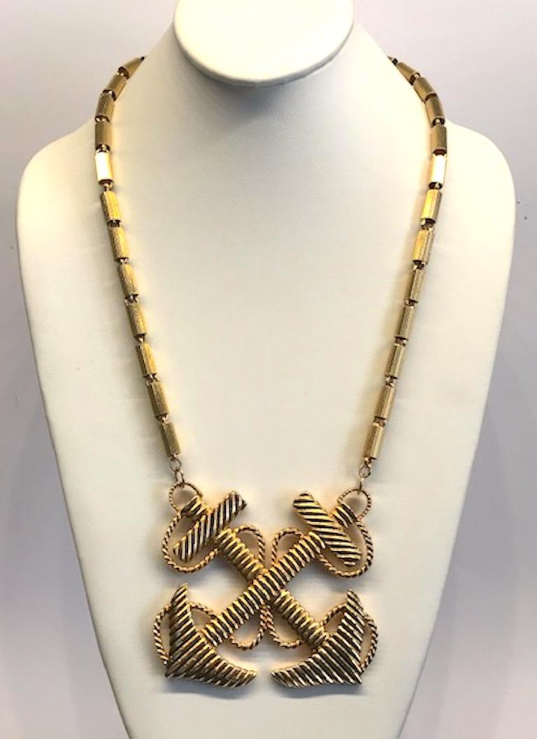 Nautical these of crossed anchors with twisted rope pendant necklace from the 1970s. The chain is a ribbed tube link with each 0.25 of an inch in diameter and 0.5 of an inch long. The pendant measures 3.25 inches wide and 3 inches high. End to end