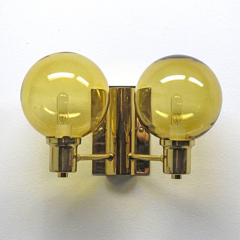Wonderful Swedish double arm wall lights by Hans Agne Jakobsen with amber colored cut glass shades, custom backplate for US j-boxes, rewired for US, two E12 sockets per fixture, max. wattage 40w per socket, bulbs provided as a one time courtesy.