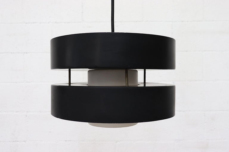 Phillips double barreled pendant light with black enameled exterior, bone white interior and milk glass inner shade. Modern two-tiered design with European candelabra sockets on top and a medium base socket below. (US candelabra adapters provided)