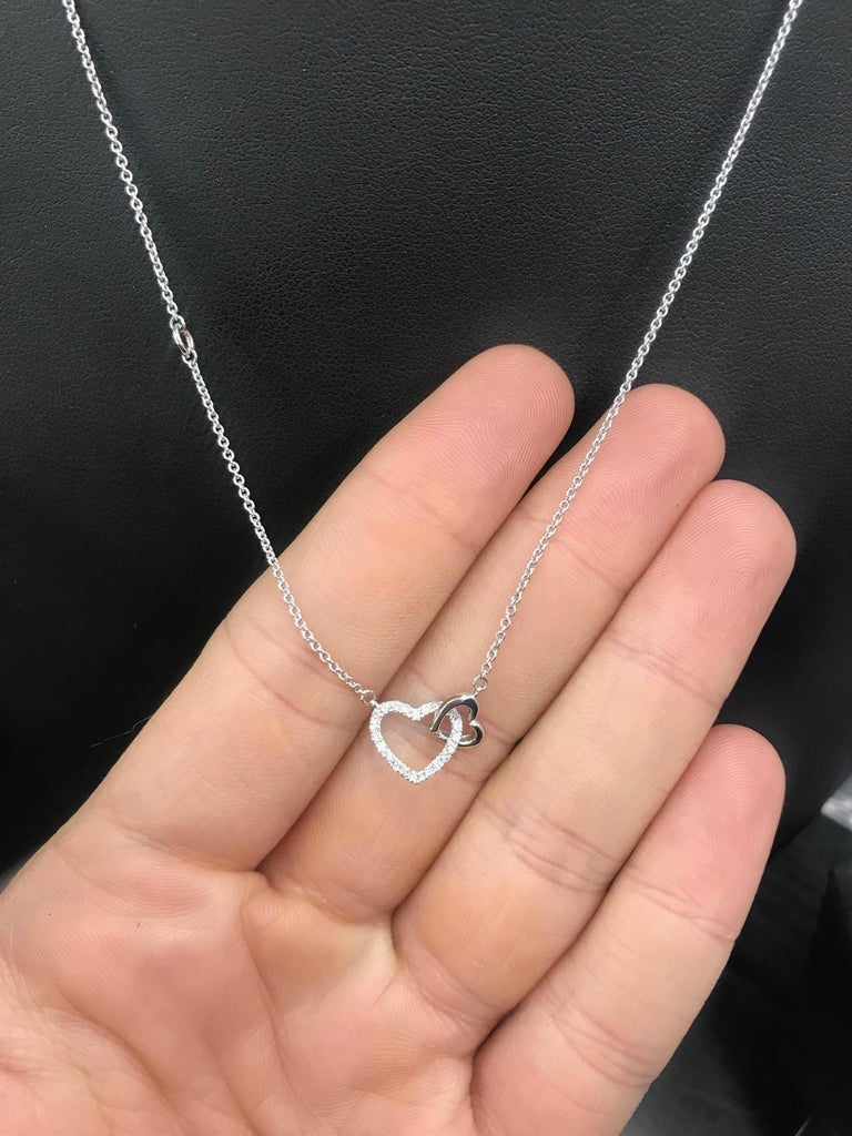 14K White gold double heart necklace featuring round brilliants weighing 0.11 carats.